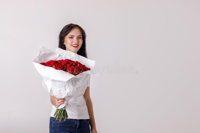 Όμορφη νέα γυναίκα με μια μεγάλη ανθοδέσμη των κόκκινων τριαντάφυλλων στοκ εικόνες με δικαίωμα ελεύθερης χρήσης