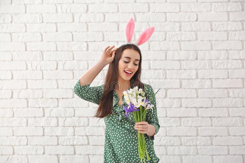 Όμορφη νέα γυναίκα με τα αυτιά λαγουδάκι Πάσχας και την ανθοδέσμη των λουλουδιών ενάντια στον άσπρο τουβλότοιχο στοκ φωτογραφίες με δικαίωμα ελεύθερης χρήσης