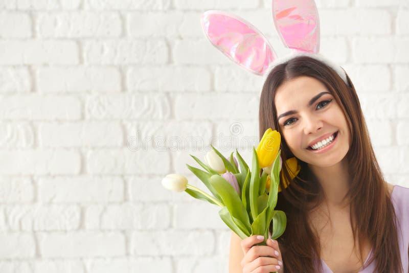Όμορφη νέα γυναίκα με τα αυτιά λαγουδάκι Πάσχας και την ανθοδέσμη των λουλουδιών ενάντια στον άσπρο τουβλότοιχο στοκ φωτογραφία με δικαίωμα ελεύθερης χρήσης
