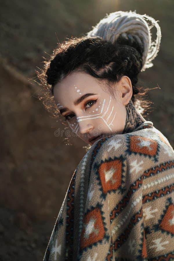 Όμορφη νέα γυναίκα με τα αυτιά νεραιδών, dreadlocks και εθνικό poncho, με το χρωματισμένο πρόσωπο Τοποθέτηση ενάντια σε μια αμμώδ στοκ εικόνα