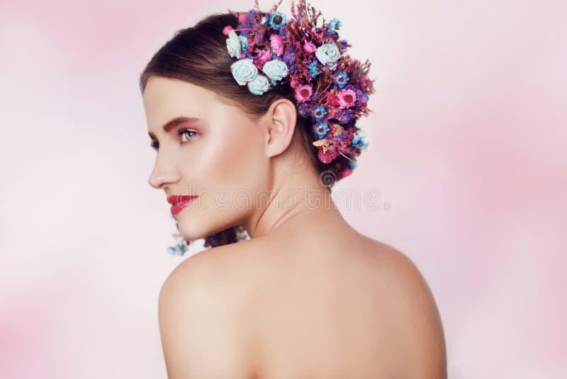 Όμορφη νέα γυναίκα με τα λεπτά λουλούδια στην τρίχα τους Κορίτσι ομορφιάς με τα λουλούδια hairstyle Πρότυπο πορτρέτο με το καλοκα στοκ εικόνες