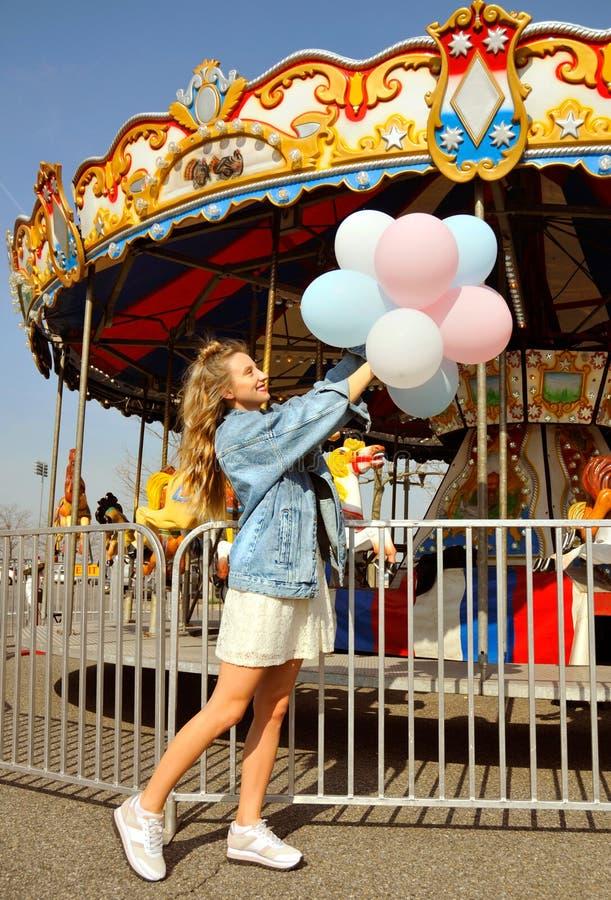 Όμορφη νέα γυναίκα με τα μπαλόνια στο λούνα παρκ στοκ εικόνες
