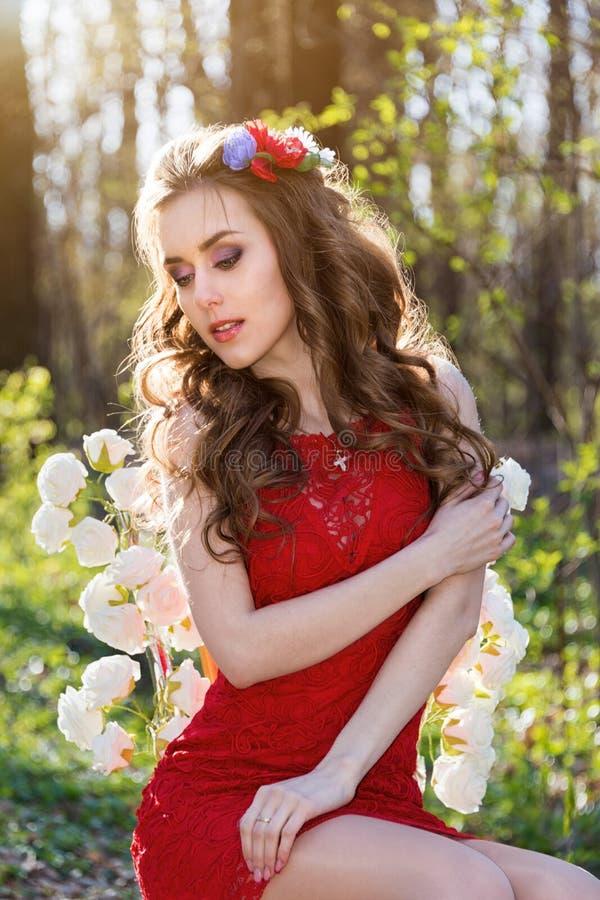Όμορφη νέα γυναίκα με τα λουλούδια στην τρίχα της στα ξύλα στοκ φωτογραφία