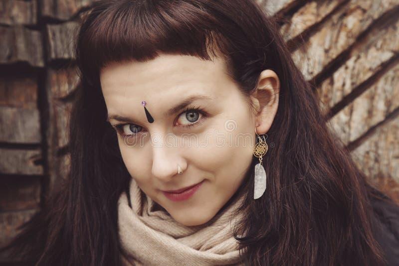 Όμορφη νέα γυναίκα με τα πνευματικά σκουλαρίκια στοκ εικόνες