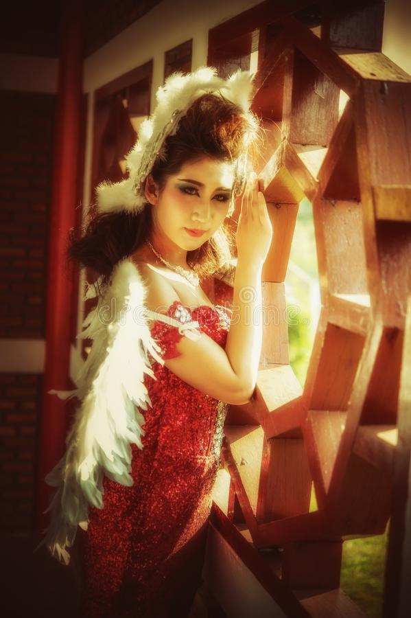 Όμορφη νέα γυναίκα με τα φτερά γωνίας του κόκκινου φορέματος που θέτουν πλησίον στοκ εικόνες με δικαίωμα ελεύθερης χρήσης
