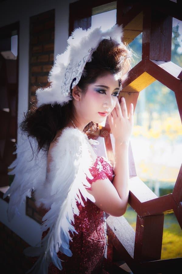 Όμορφη νέα γυναίκα με τα φτερά γωνίας του κόκκινου φορέματος που θέτουν πλησίον στοκ εικόνες