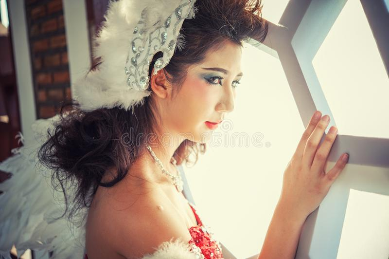 Όμορφη νέα γυναίκα με τα φτερά γωνίας του κόκκινου φορέματος που θέτουν πλησίον στοκ εικόνα