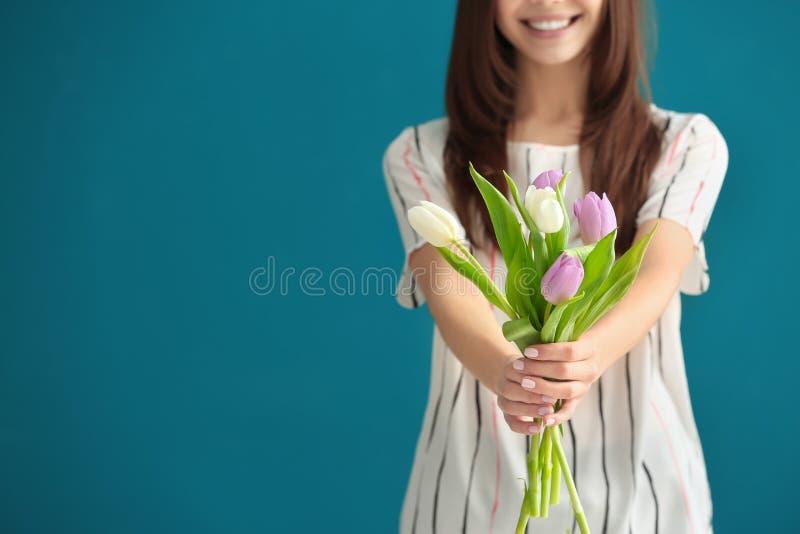 Όμορφη νέα γυναίκα με την ανθοδέσμη των τουλιπών στο υπόβαθρο χρώματος, κινηματογράφηση σε πρώτο πλάνο στοκ φωτογραφία