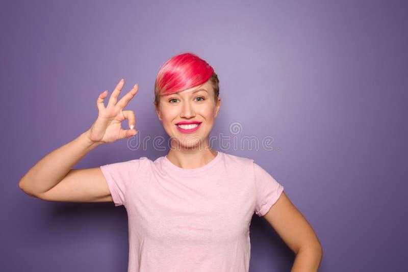 Όμορφη νέα γυναίκα με την ασυνήθιστη τρίχα που παρουσιάζει ΕΝΤΑΞΕΙ χειρονομία στο υπόβαθρο χρώματος στοκ εικόνες
