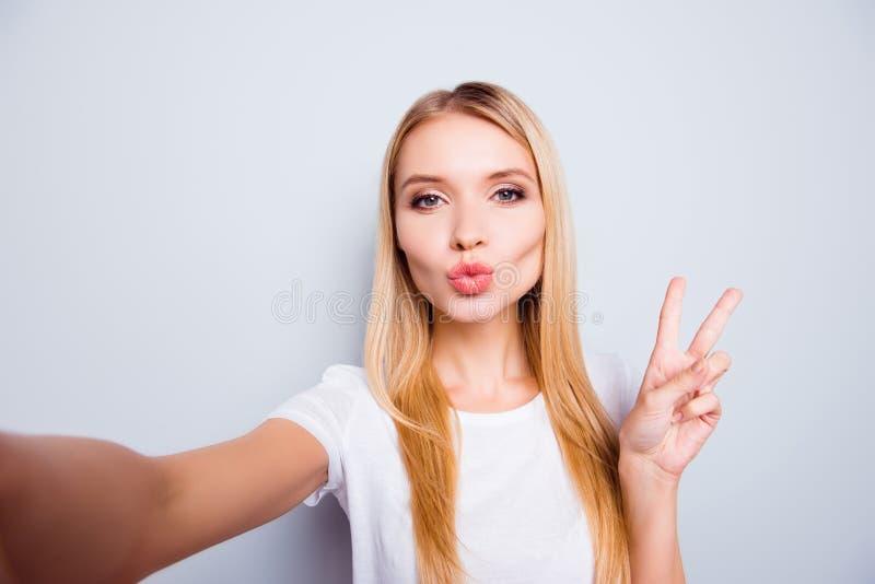 Όμορφη νέα όμορφη γυναίκα με την ευθεία ξανθή τρίχα που στέλνει το α στοκ εικόνα με δικαίωμα ελεύθερης χρήσης