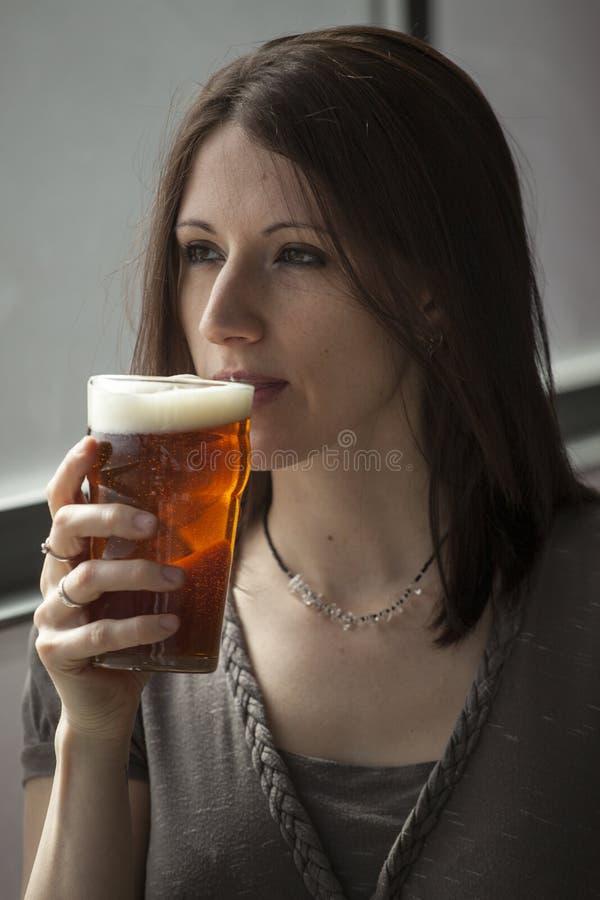 Όμορφη νέα γυναίκα με την καφετιά τρίχα που πίνει μια πίντα στοκ εικόνα