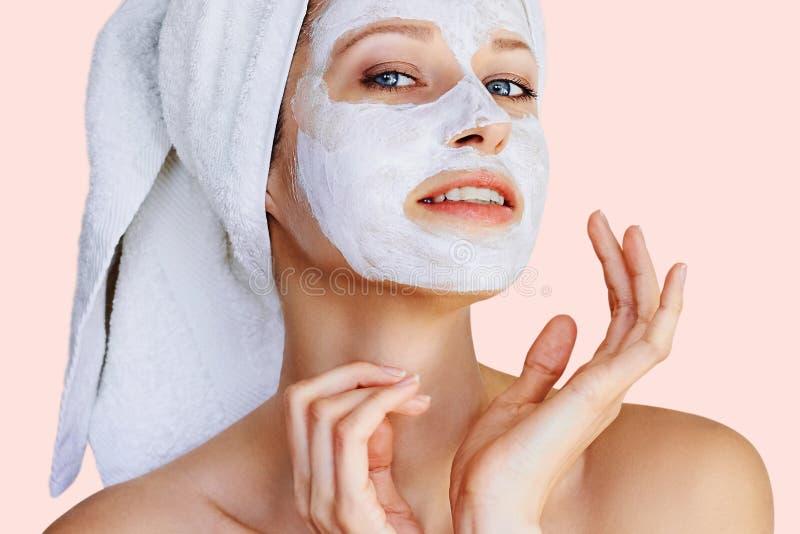 Όμορφη νέα γυναίκα με την του προσώπου μάσκα στο πρόσωπό της Φροντίδα δέρματος και επεξεργασία, SPA, φυσικές ομορφιά και cosmetol στοκ εικόνα
