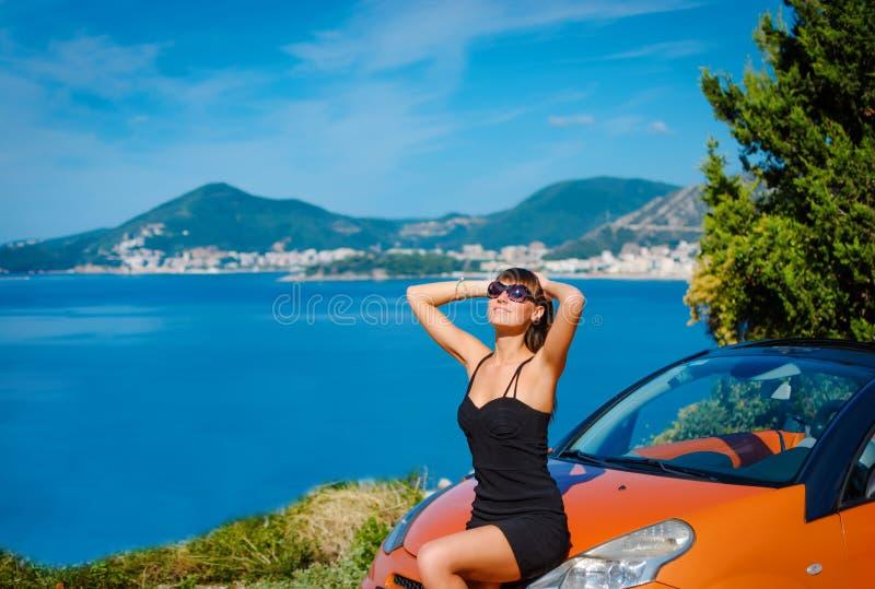 Όμορφη νέα γυναίκα με τη μακρυμάλλη συνεδρίαση στο πορτοκαλί καμπριολέ στην ακτή Μεσογείων στοκ εικόνες με δικαίωμα ελεύθερης χρήσης