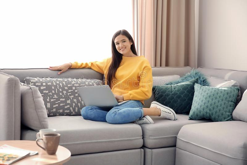 Όμορφη νέα γυναίκα με τη συνεδρίαση lap-top στον καναπέ στοκ εικόνα