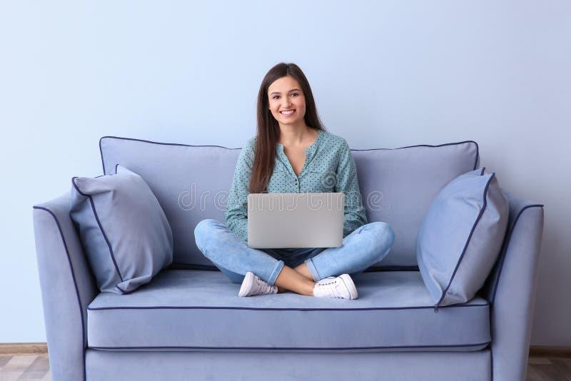 Όμορφη νέα γυναίκα με τη συνεδρίαση lap-top στον καναπέ στοκ εικόνες
