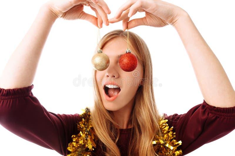 Όμορφη νέα γυναίκα με τις σφαίρες Χριστουγέννων πέρα από το άσπρο υπόβαθρο στοκ φωτογραφία