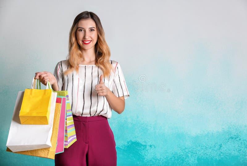 Όμορφη νέα γυναίκα με τις τσάντες αγορών που παρουσιάζουν αντίχειρας-επάνω στο υπόβαθρο χρώματος στοκ εικόνες