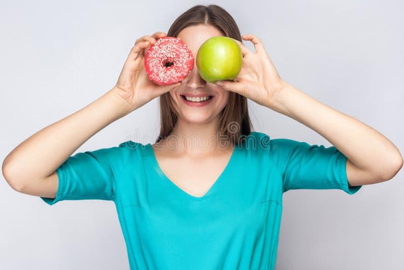 Όμορφη νέα γυναίκα με τις φακίδες στο πράσινο φόρεμα, που κρατά μπροστά στα μάτια της το πράσινο μήλο και ρόδινο doughnut με το ο στοκ φωτογραφίες