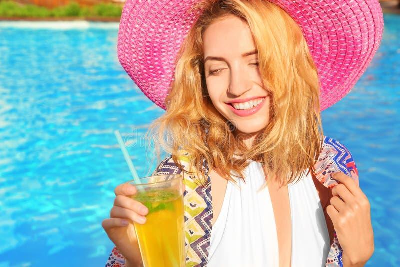 Όμορφη νέα γυναίκα με το γυαλί της πισίνας λεμονάδας πλησίον στοκ φωτογραφία με δικαίωμα ελεύθερης χρήσης