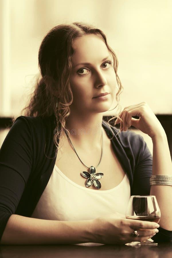 Όμορφη νέα γυναίκα με το γυαλί κονιάκ στο εστιατόριο στοκ εικόνα με δικαίωμα ελεύθερης χρήσης