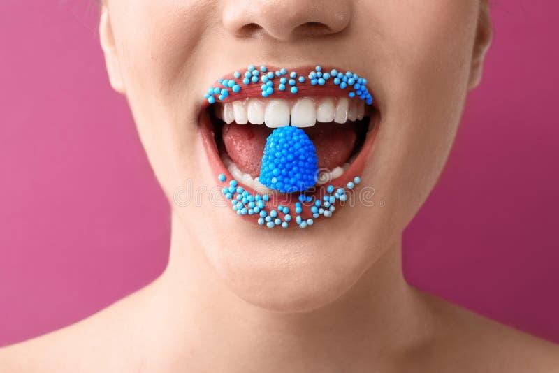 Όμορφη νέα γυναίκα με το δημιουργικό makeup και καραμέλα στο στόμα στο υπόβαθρο χρώματος, κινηματογράφηση σε πρώτο πλάνο στοκ φωτογραφίες με δικαίωμα ελεύθερης χρήσης