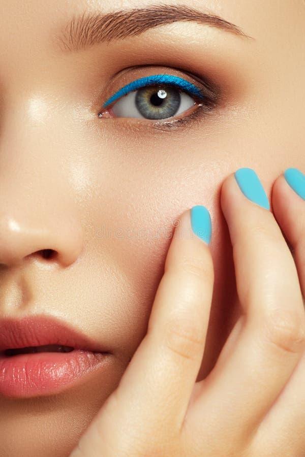 Όμορφη νέα γυναίκα με το καθιερώνον τη μόδα μπλε makeup ανασκόπησης ομορφιάς μπλε έννοιας εμπορευματοκιβωτίων καλλυντικός βάθους  στοκ φωτογραφία με δικαίωμα ελεύθερης χρήσης