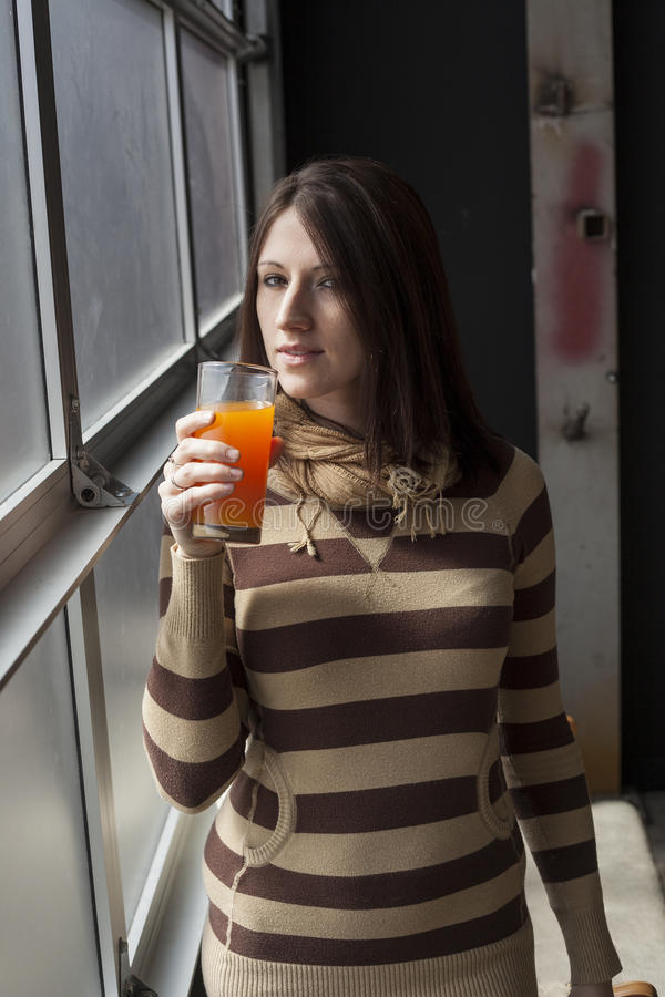 Όμορφη νέα γυναίκα με το καφετί ποτήρι κατανάλωσης τρίχας του μάγκο Ju στοκ εικόνες