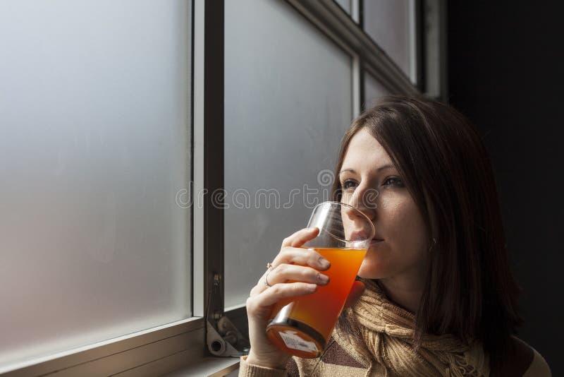 Όμορφη νέα γυναίκα με το καφετί ποτήρι κατανάλωσης τρίχας του μάγκο Ju στοκ εικόνες με δικαίωμα ελεύθερης χρήσης