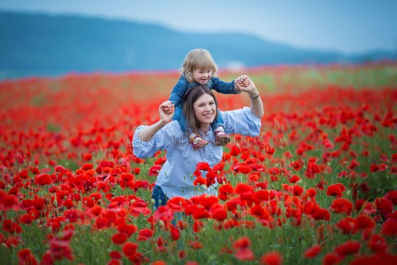 Όμορφη νέα γυναίκα με το κορίτσι παιδιών στον τομέα παπαρουνών ευτυχής οικογένεια που έχει τη διασκέδαση στη φύση υπαίθριο πορτρέ στοκ φωτογραφία με δικαίωμα ελεύθερης χρήσης