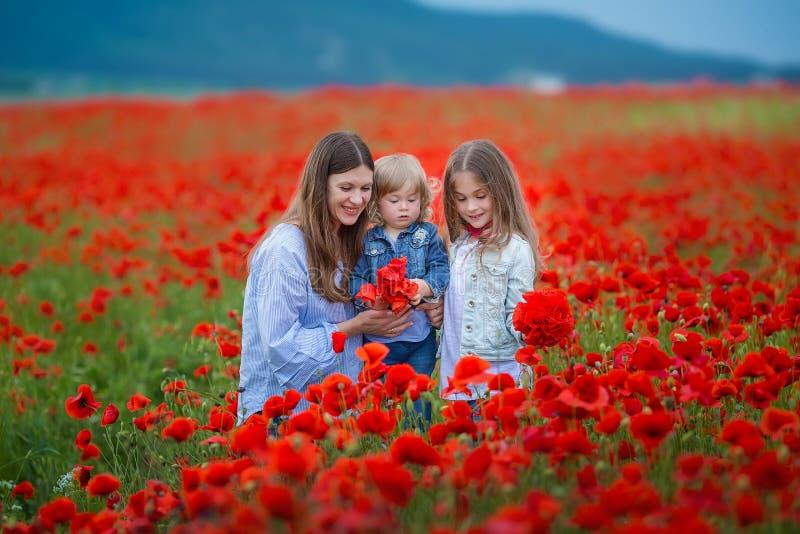 Όμορφη νέα γυναίκα με το κορίτσι παιδιών στον τομέα παπαρουνών ευτυχής οικογένεια που έχει τη διασκέδαση στη φύση υπαίθριο πορτρέ στοκ εικόνα