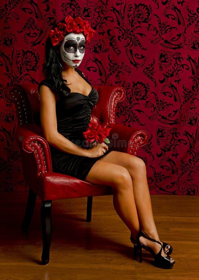 Όμορφη νέα γυναίκα με το κρανίο ζάχαρης που περιβάλλεται από το κόκκινο στοκ φωτογραφία με δικαίωμα ελεύθερης χρήσης