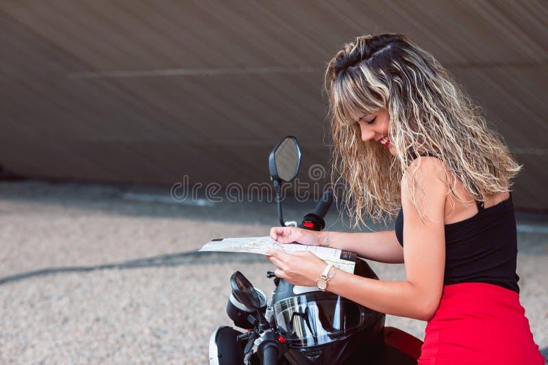 Όμορφη νέα γυναίκα με το χάρτη διαθέσιμο και μια μοτοσικλέτα στοκ εικόνες