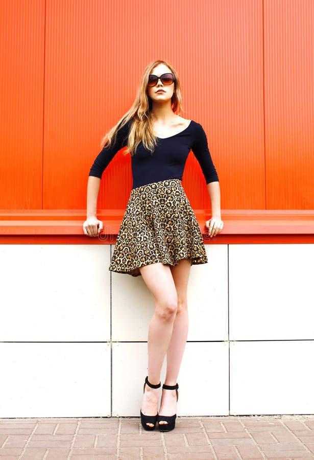 Όμορφη νέα γυναίκα μόδας στη φούστα λεοπαρδάλεων και γυαλιά ηλίου πέρα από το κόκκινο στοκ εικόνες