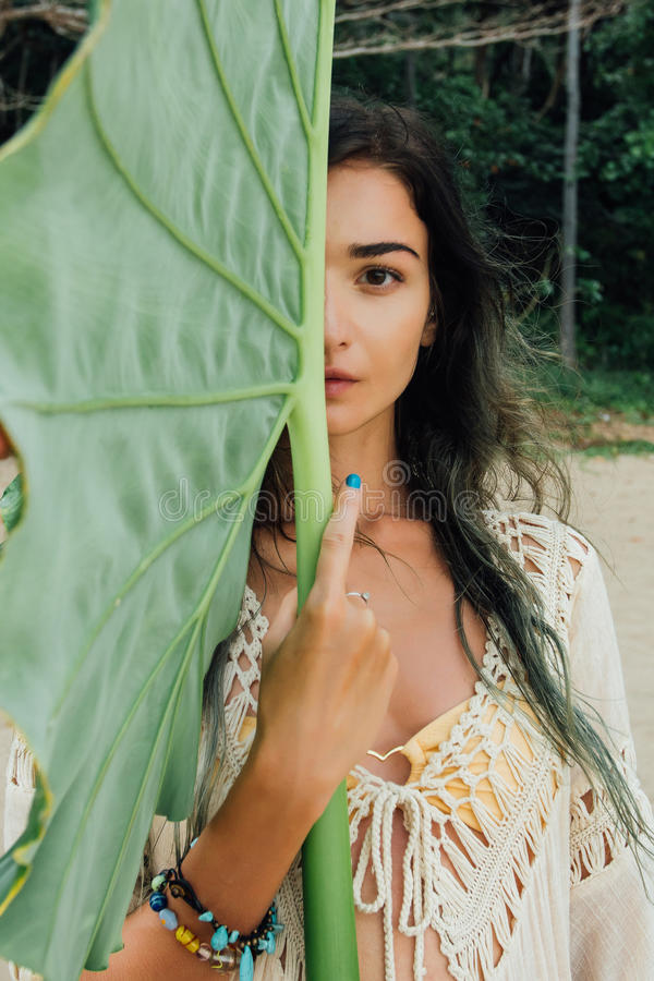 Όμορφη νέα γυναίκα πορτρέτου ενάντια στο μεγάλο πράσινο τροπικό δέντρο φύλλων στοκ εικόνα