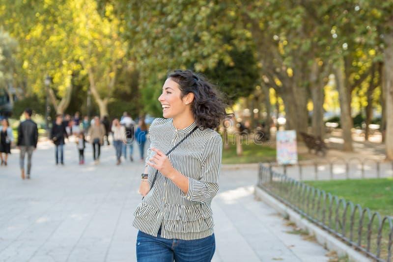 Όμορφη νέα γυναίκα που έχει τη διασκέδαση στο πάρκο στοκ εικόνες