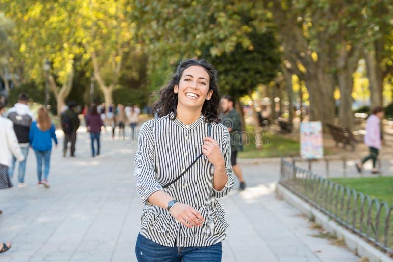 Όμορφη νέα γυναίκα που έχει τη διασκέδαση στο πάρκο στοκ φωτογραφίες