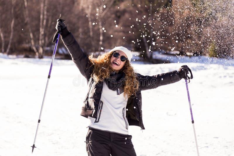 Όμορφη νέα γυναίκα που έχει τη διασκέδαση πέρα από το χειμερινό υπόβαθρο στοκ φωτογραφία