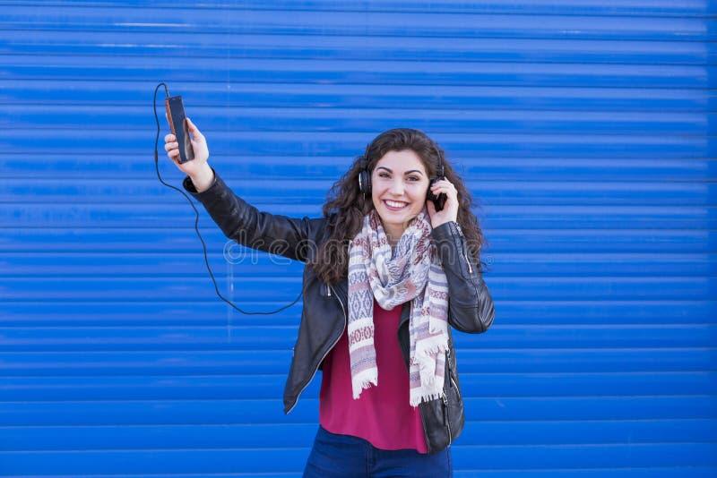 Όμορφη νέα γυναίκα που ακούει τη μουσική στο κινητό τηλέφωνό της με την κάσκα και που έχει τη διασκέδαση πέρα από το μπλε υπόβαθρ στοκ εικόνες