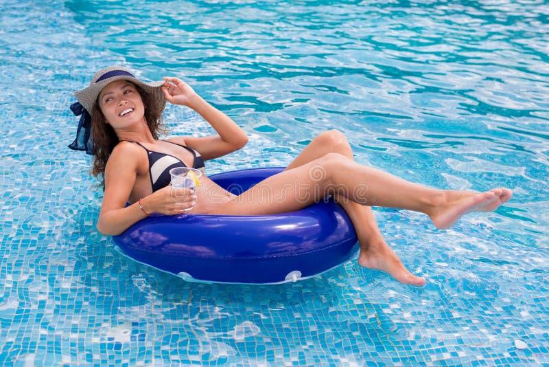 Όμορφη νέα γυναίκα που απολαμβάνει ένα ποτό στην πισίνα στοκ εικόνες