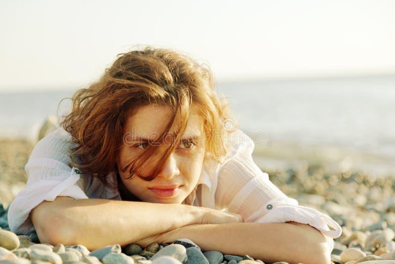 Όμορφη νέα γυναίκα που βρίσκεται στην παραλία στοκ φωτογραφία