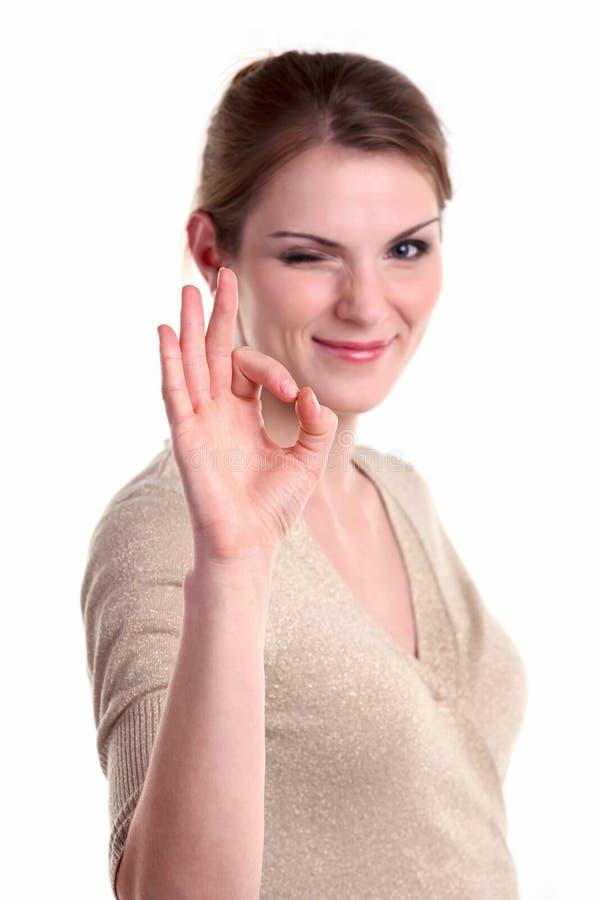 Όμορφη νέα γυναίκα που δίνει το εντάξει σημάδι και το κλείσιμο του ματιού στοκ φωτογραφία με δικαίωμα ελεύθερης χρήσης