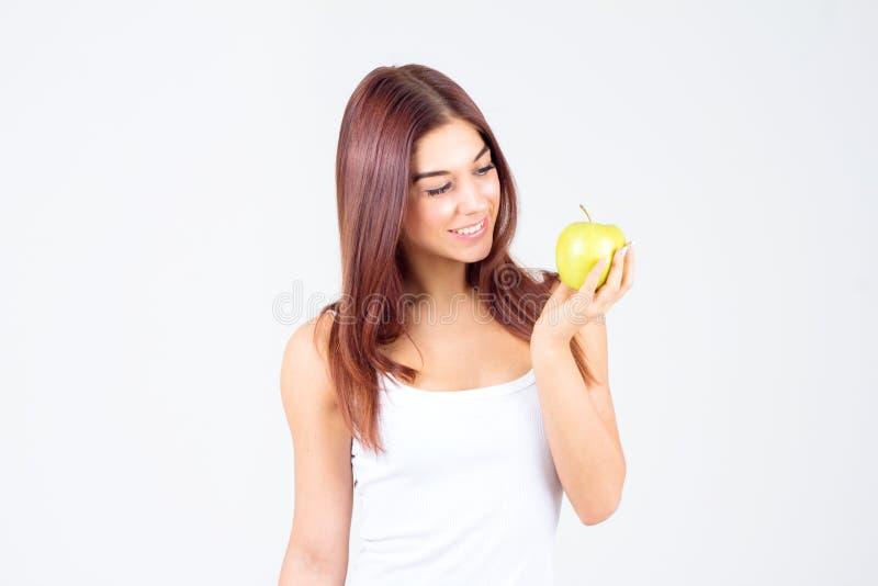 Όμορφη νέα γυναίκα που εξετάζει το μήλο Υγιής τρόπος ζωής στοκ εικόνες