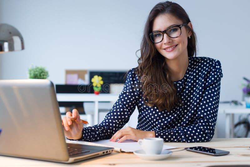 Όμορφη νέα γυναίκα που εργάζεται με το lap-top στο γραφείο της στοκ εικόνα