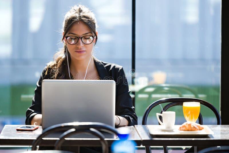 Όμορφη νέα γυναίκα που εργάζεται με το lap-top της ενώ έχοντας το πρόγευμα σε μια καφετερία στοκ φωτογραφία