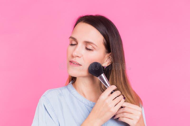 Όμορφη νέα γυναίκα που εφαρμόζει την καλλυντική σκόνη στο πρόσωπό της με το θύσανο, έννοια φροντίδας δέρματος στοκ φωτογραφία με δικαίωμα ελεύθερης χρήσης