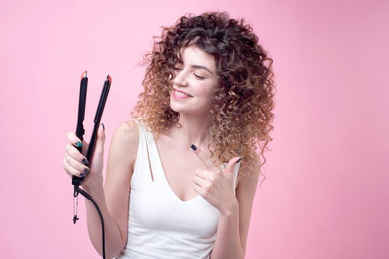 Όμορφη νέα γυναίκα που κάνει τις μπούκλες με το κατσάρωμα του σιδήρου στοκ φωτογραφία με δικαίωμα ελεύθερης χρήσης