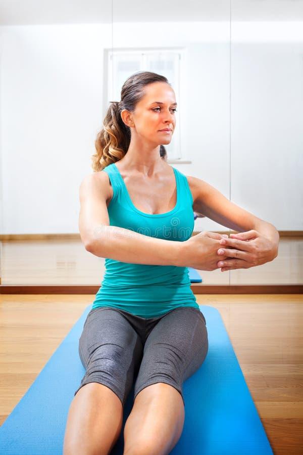 Όμορφη νέα γυναίκα που κάνει το τέντωμα ασκήσεων ικανότητας στοκ εικόνα