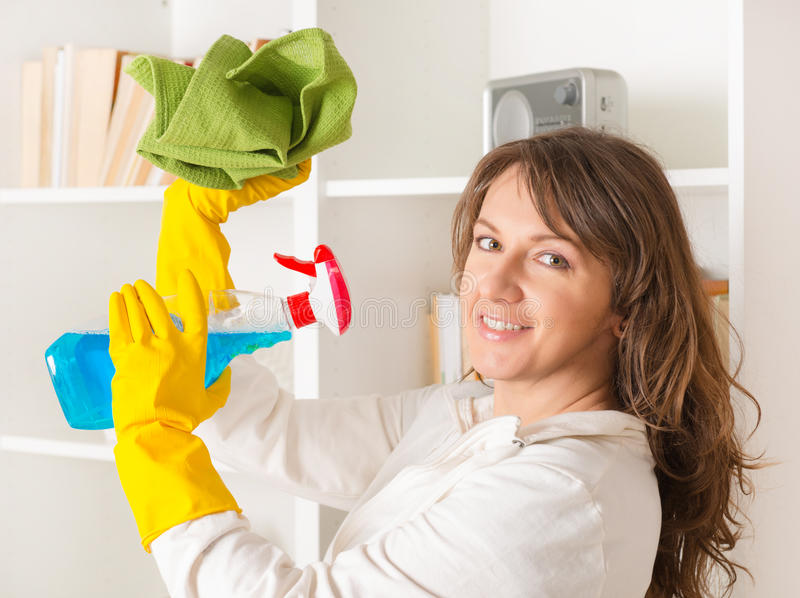 Όμορφη νέα γυναίκα που καθαρίζει το σπίτι της στοκ εικόνα