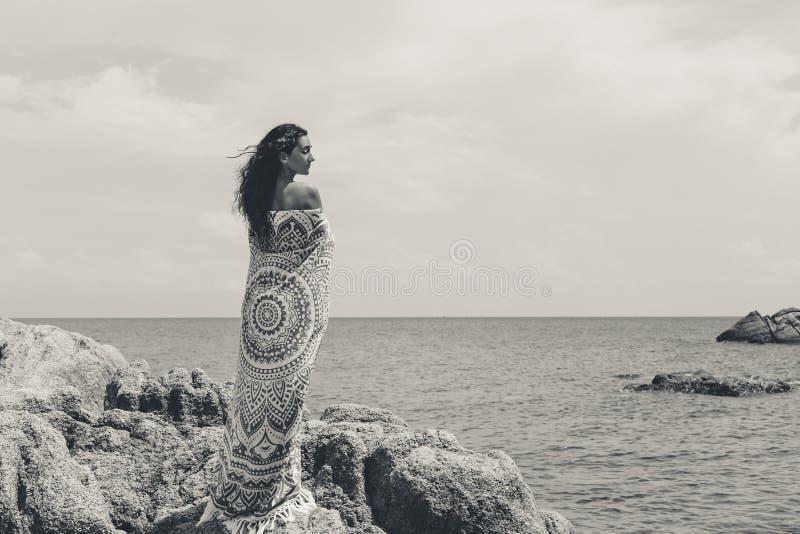 Όμορφη νέα γυναίκα που καλύπτεται με το κάλυμμα με στην παραλία στοκ φωτογραφία