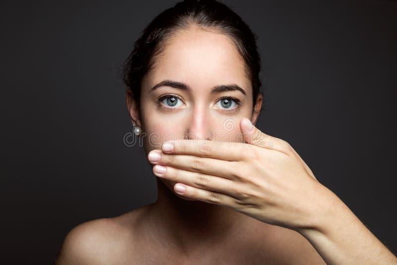 Όμορφη νέα γυναίκα που καλύπτει το στόμα της με το χέρι απομονωμένος στοκ εικόνες